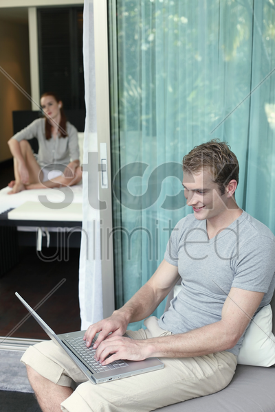 man using laptop, woman listening to music in the background stock photo