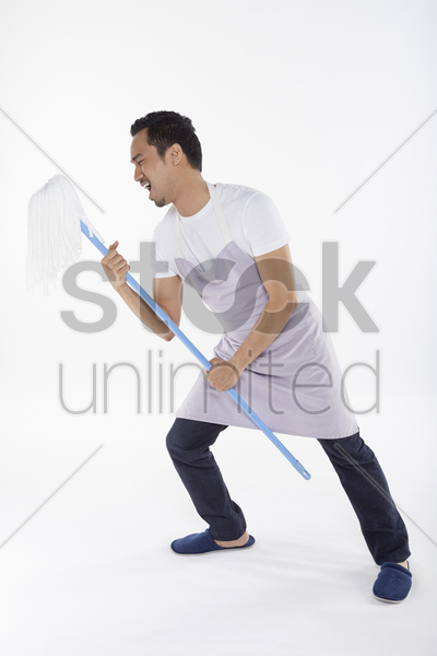man using mop as an imaginary microphone stock photo