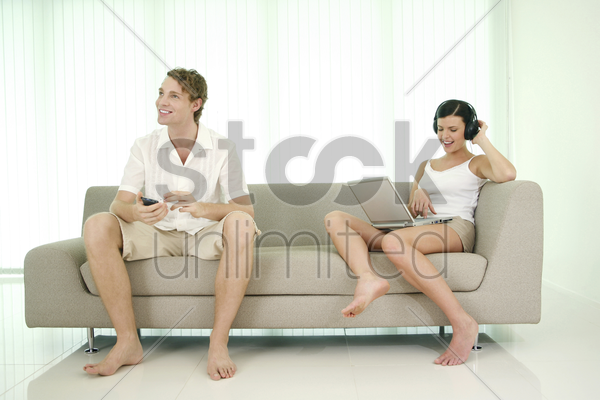 man using palmtop while his girlfriend is listening to music and using laptop stock photo