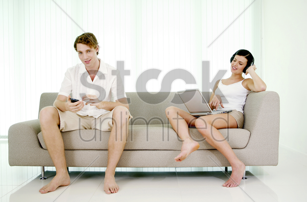 man using pda phone while woman listening to music on the headphones stock photo