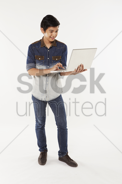 man using the laptop while standing stock photo