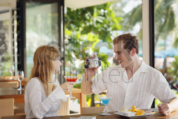 man using video camera to record woman holding cocktail drink stock photo