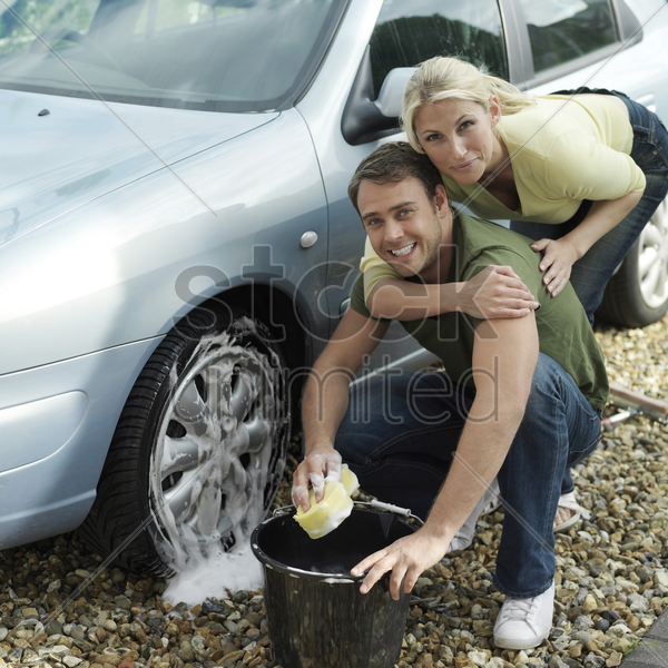man washing car wheel, woman hugging him from behind stock photo