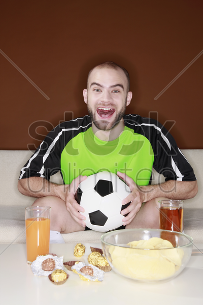 man watching football match on the television stock photo