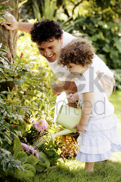 man watching his daughter watering plants stock photo