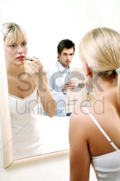 man watching his wife applying lipstick stock photo