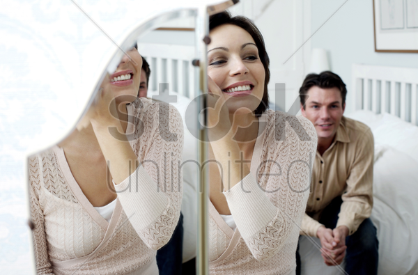 man watching his wife looking at the mirror applying make-up stock photo