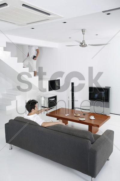 man watching television in the living room stock photo