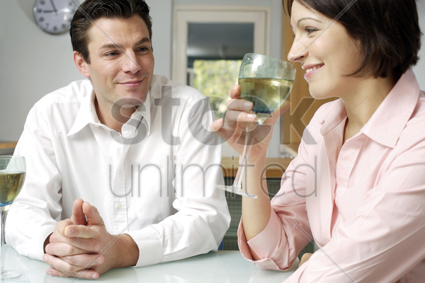 man watching wife drinking wine stock photo
