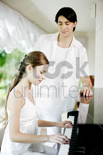 man watching woman playing piano stock photo