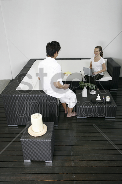 man watching woman sitting on the couch using laptop stock photo