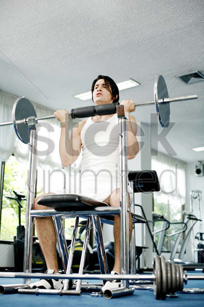man weight lifting in the gymnasium stock photo