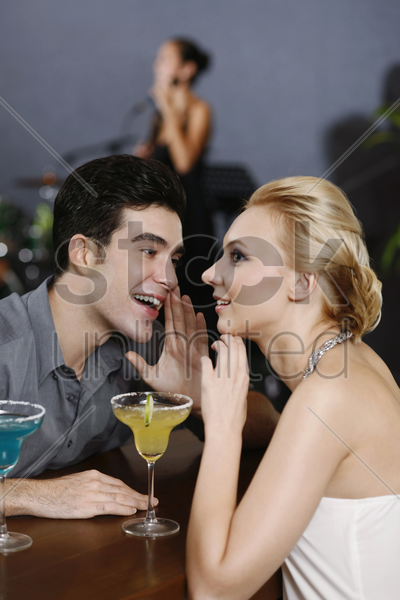 man whispering into woman's ear stock photo