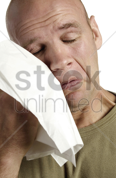 man wiping his tears with a tissue stock photo