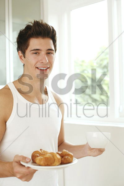 man with a cup of coffee and a plate of croissants stock photo