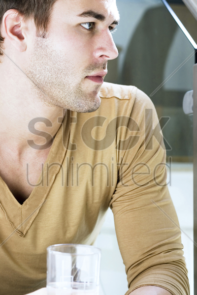man with a glass of water thinking stock photo