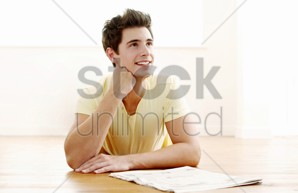 man with a newspaper on the table smiling while daydreaming stock photo