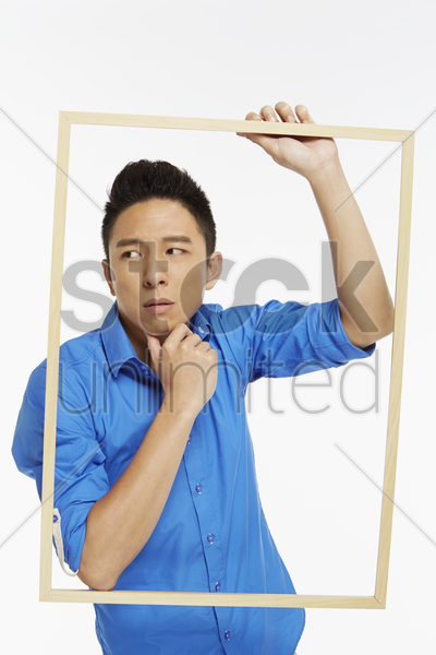 man with a picture frame, contemplating stock photo
