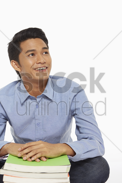 man with a stack of books stock photo