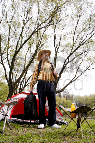 man with cowboy hat camping in the park stock photo