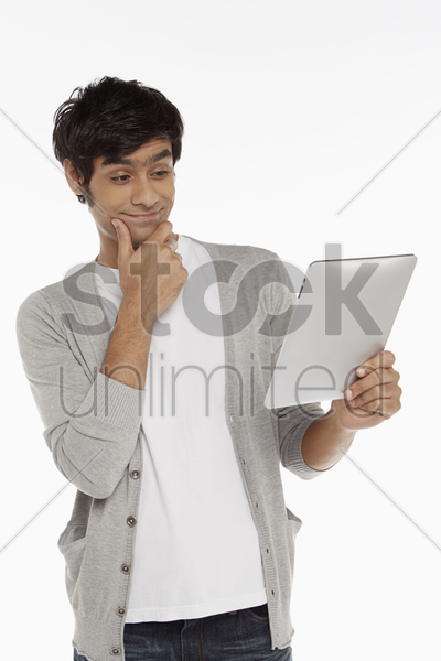 man with digital tablet, contemplating stock photo