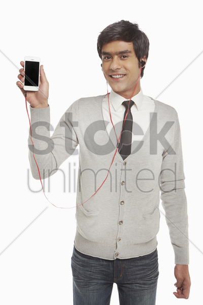 man with earphone holding up a mobile phone stock photo