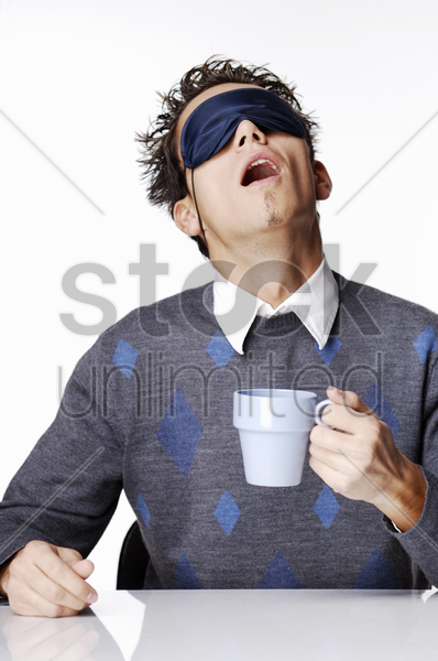 man with eye mask holding a cup of coffee stock photo