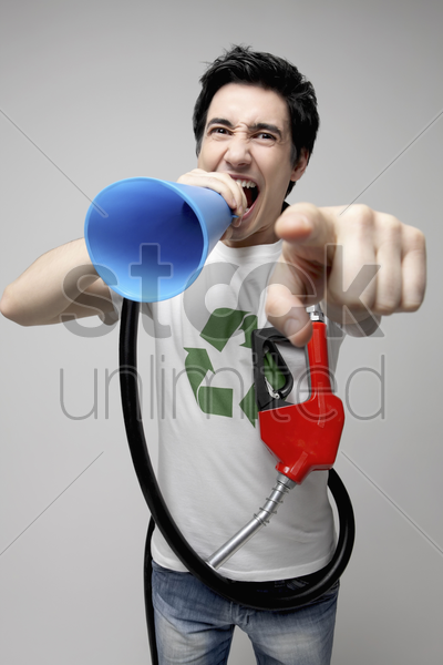 man with gas pump shouting through a megaphone stock photo