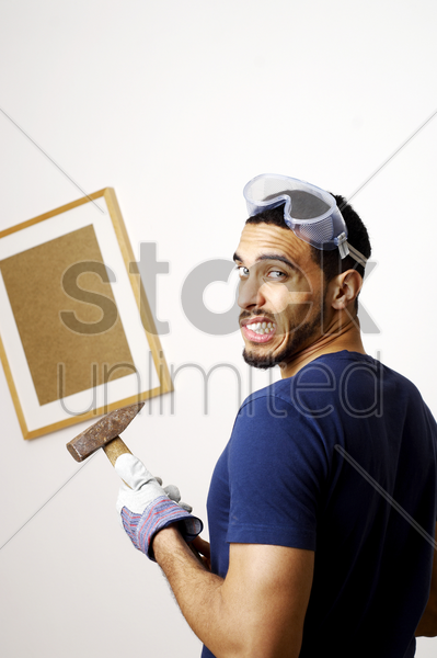 man with goggles holding a hammer stock photo