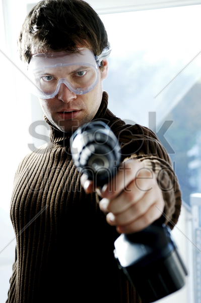 man with goggles pointing a drill at the camera stock photo