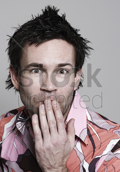 man with hand covering mouth stock photo