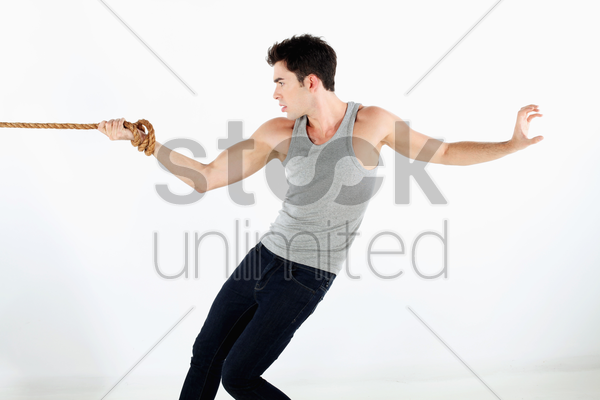 man with hand tied to a rope, pulling hard stock photo
