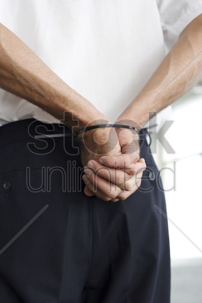 man with hands tied to the back stock photo