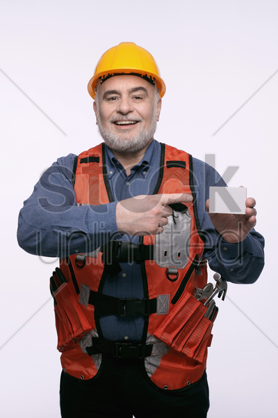 man with hardhat pointing at a business card stock photo