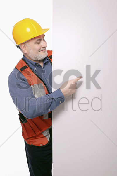 man with hardhat pointing at a placard stock photo