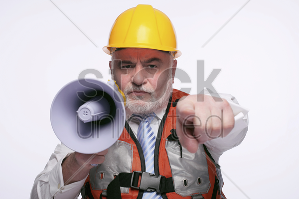 man with hardhat pointing while shouting into megaphone stock photo
