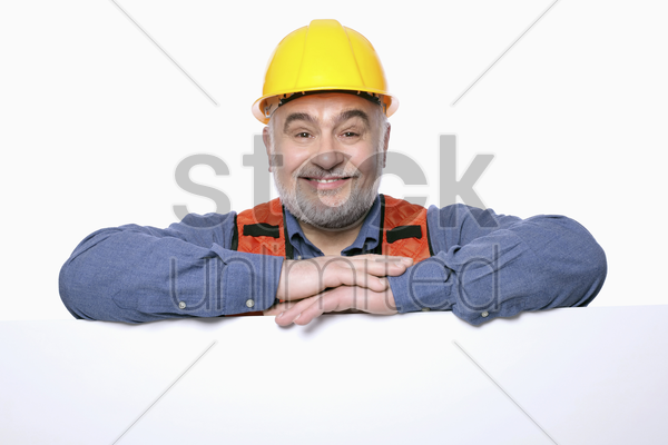 man with hardhat posing with placard stock photo