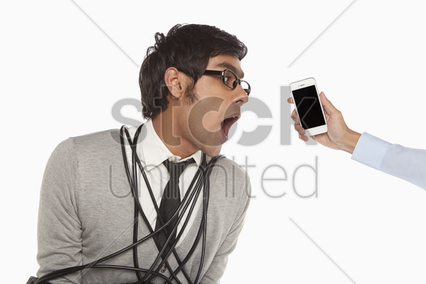 man with headset wrapped in a tangled cable, talking on the phone stock photo