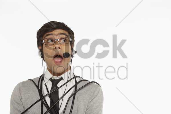 man with headset wrapped in a tangled cable stock photo