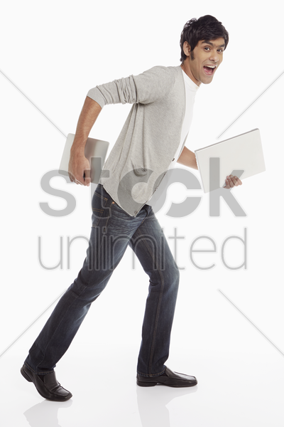 man with laptop and digital tablet showing running pose stock photo