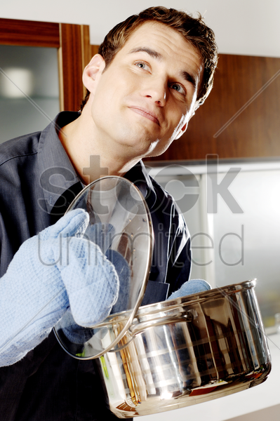 man with oven mitt holding a pot of soup stock photo