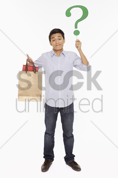 man with shopping bags holding up a question mark stock photo