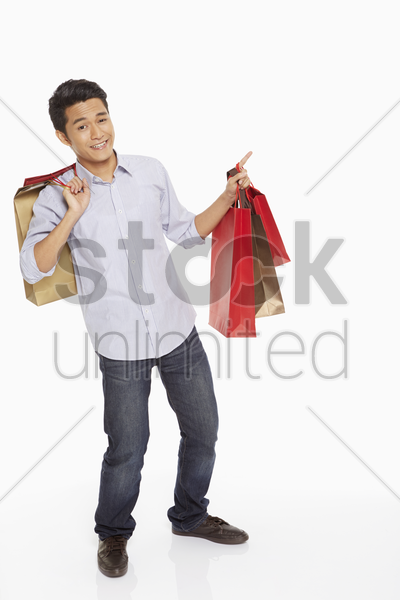 man with shopping bags pointing to the left stock photo
