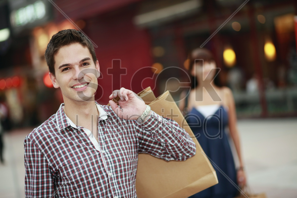 man with shopping bags smiling stock photo