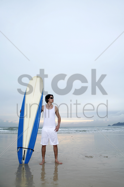 man with sunglasses holding a surfboard on the beach stock photo
