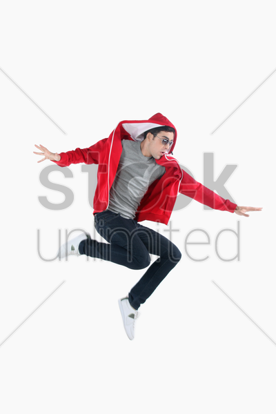 man with sunglasses jumping in the air stock photo
