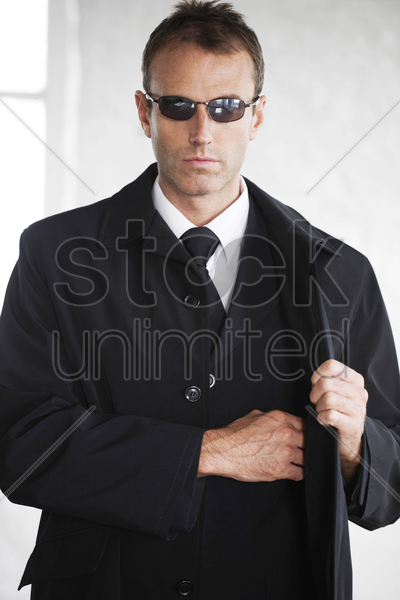 man with sunglasses taking out gun from his suit stock photo
