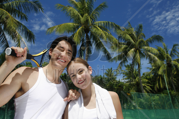 man with tennis racquet posing with his girlfriend stock photo