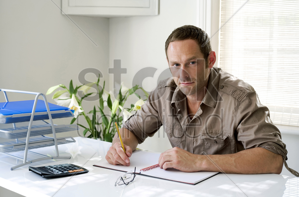 man working at his desk in a home office stock photo