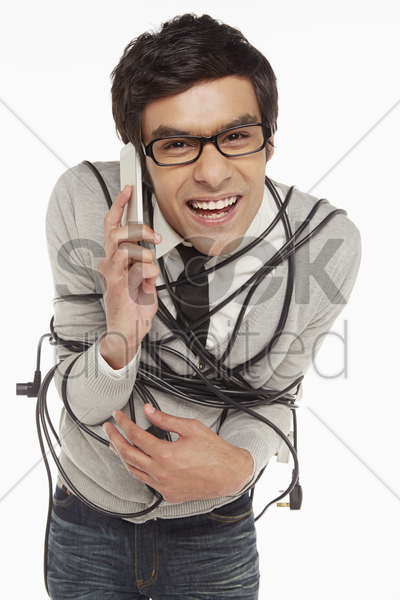 man wrapped in a tangled cable talking on the phone stock photo